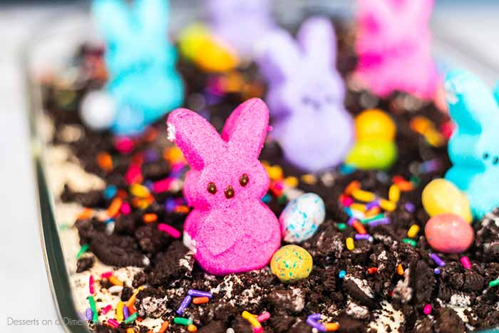 Easter dirt cake is an easy and delicious no bake treat perfect for dessert on Easter. This fun dessert is decorated with Easter peeps, candy and more.